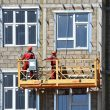 Workers on a suspended scaffold mount fasteners for a rainscreen.